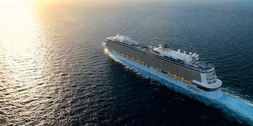 Bild tagen från ovan när fartyget Anthem of the Seas kryssar fram i det mörka vattnet i soluppgången.