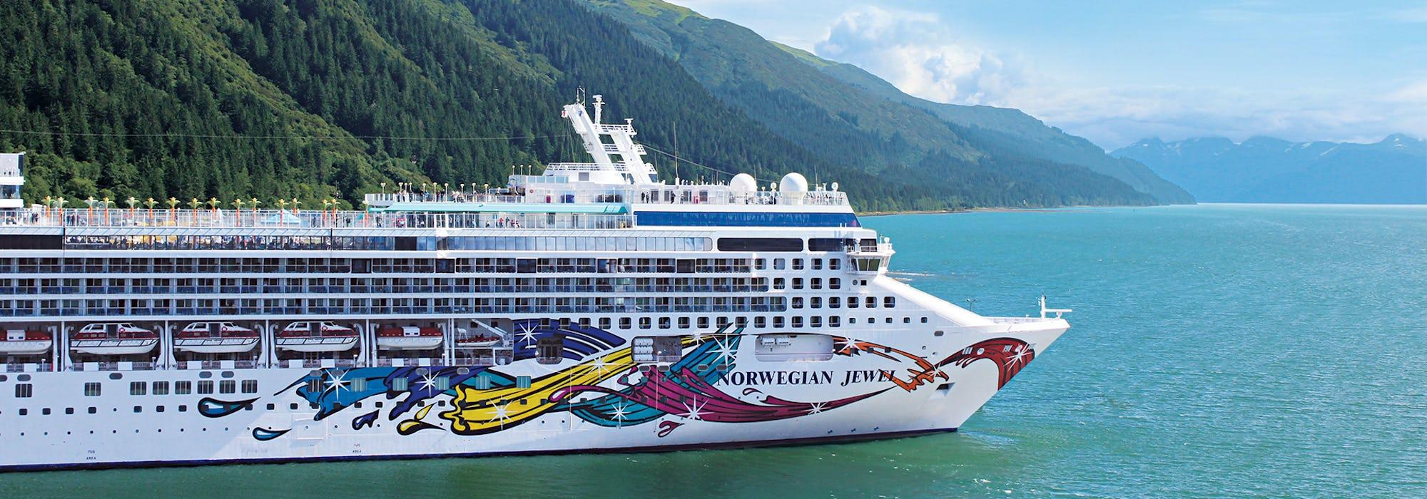Bild på Norwegian Jewel tagen från sidan med höga berg och blått vatten runtomkring.