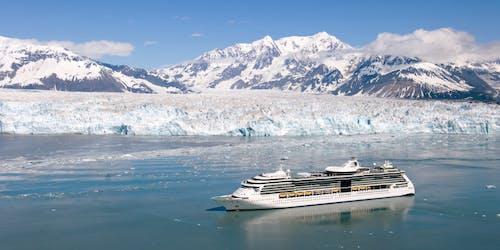Bild från ovan på Serenade of the Seas som kryssar fram vid snötäckta berg och isberg i Alaska.