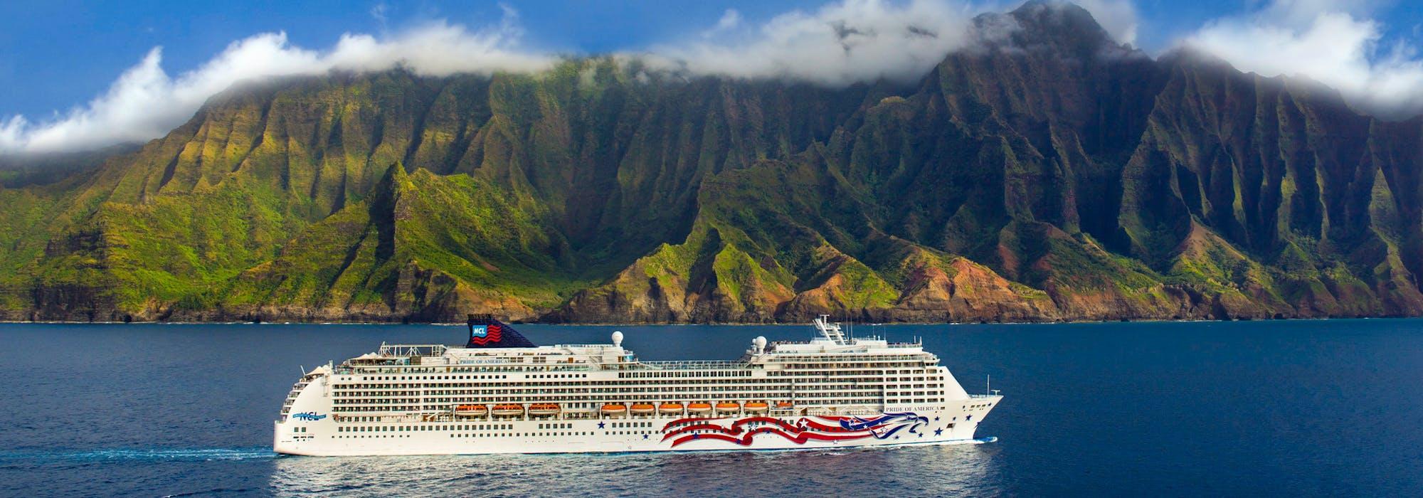 Fartyget Pride of America kryssas i det kristallblå vattnet utanför Hawaiis kust med storslagen natur och berg i bakgrunden.