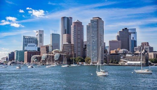 Bild på Bostons skyline med havet framför och flera segelbåtar.