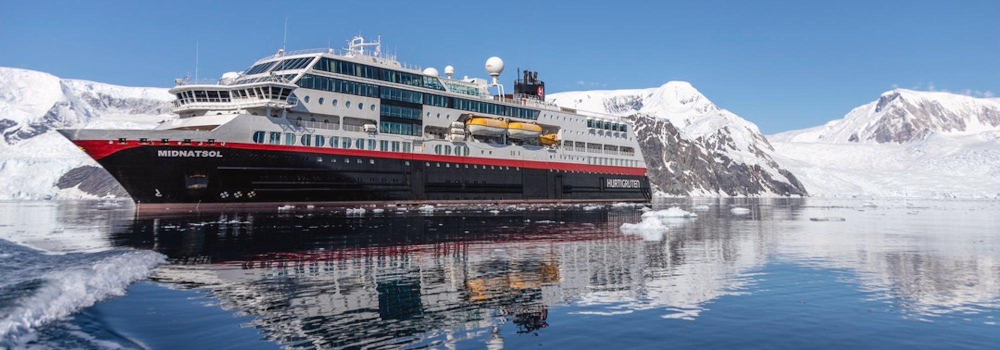Fartyget MS Eirik Raude, tidigare MS Midnatsol ligger  i vattnet med snötäckta berg runtomkring.