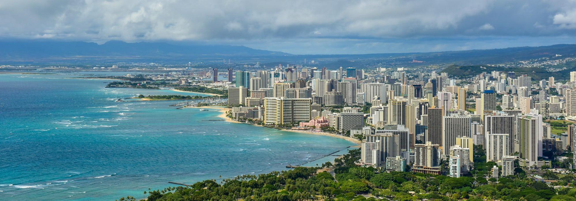 Bild tagen uppifrån på Honolulu med det ljusblå vattnet till vänster och stadens höga byggnader till vänster.