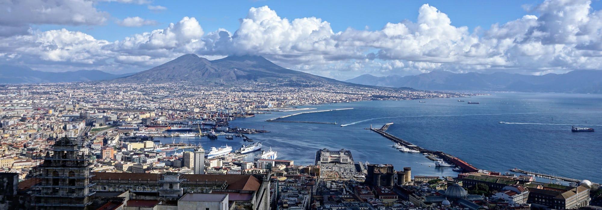 Bild från ovan på Neapels hamn med mängder av byggnader och vulkanen Vesuvius i bakgrunden.