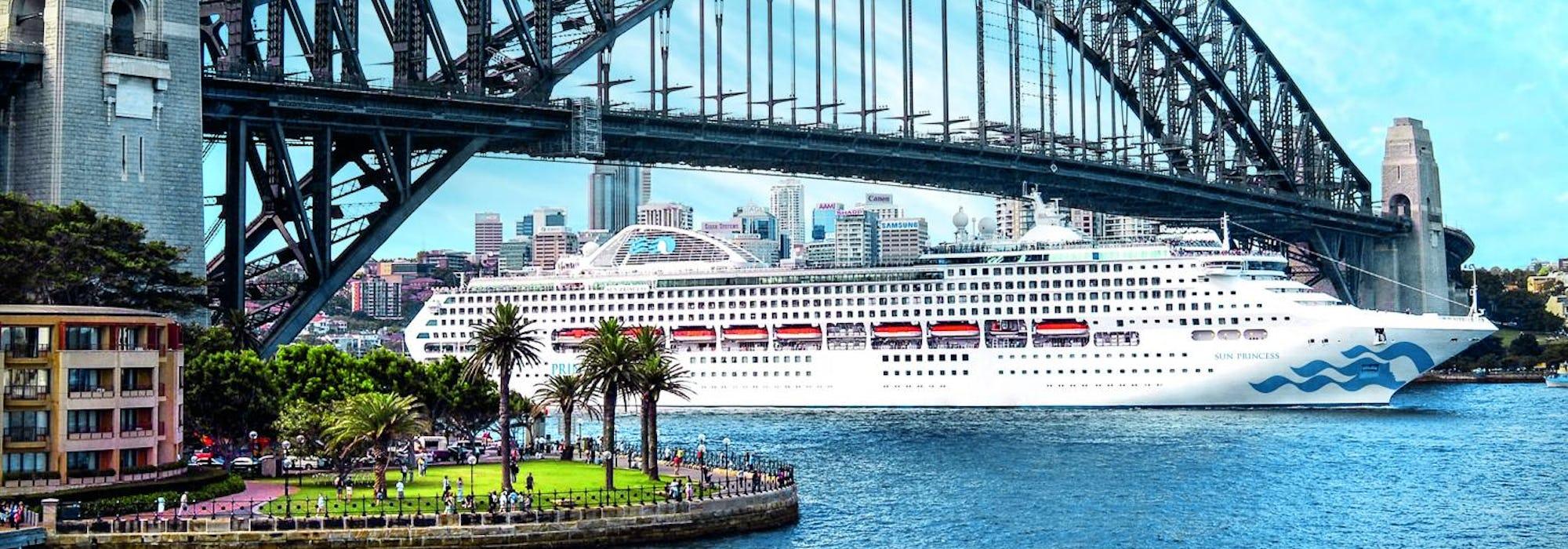 Fartyget Sun Princess kryssar fram under en blå stålbro.