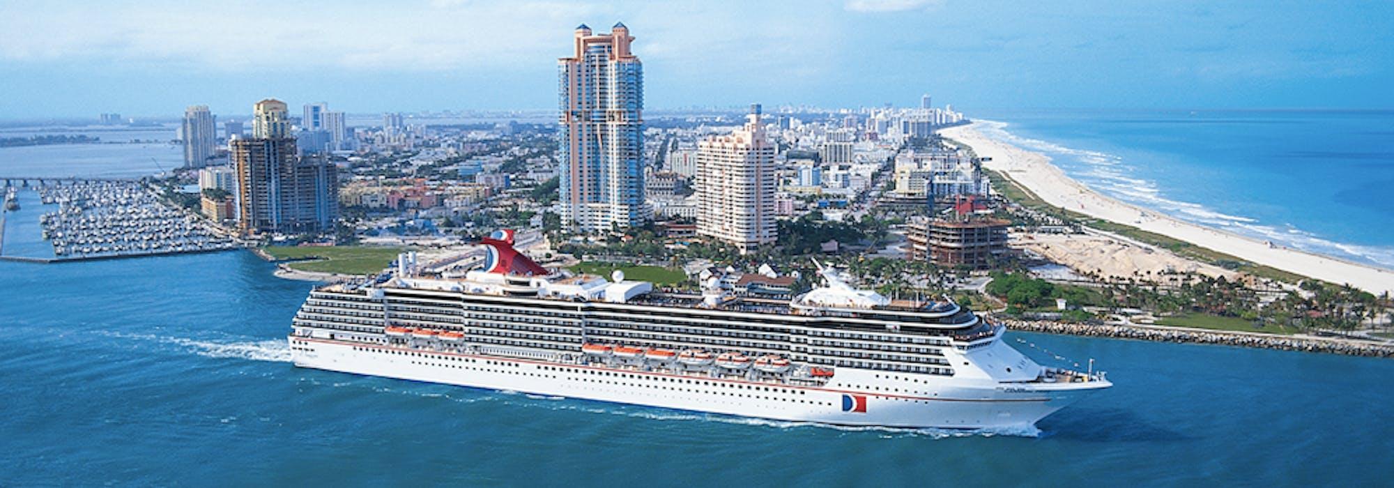 Carnival Pride kryssar förbi en stor ö med sandstrand och byggnader.