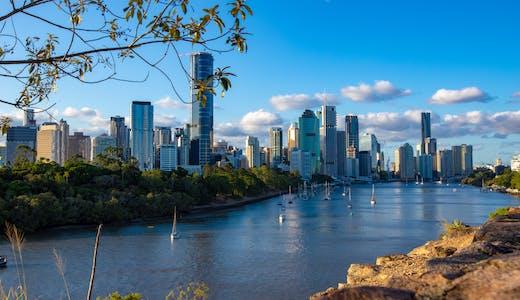 Bild på Brisbane med segelbåtar i vattnet, höghus och vacker natur.