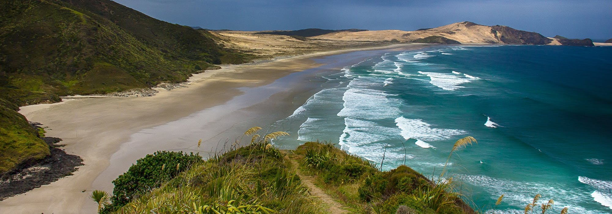 Otroligt vacker natur med vågorna som sköljer upp på stranden som omges av berg.