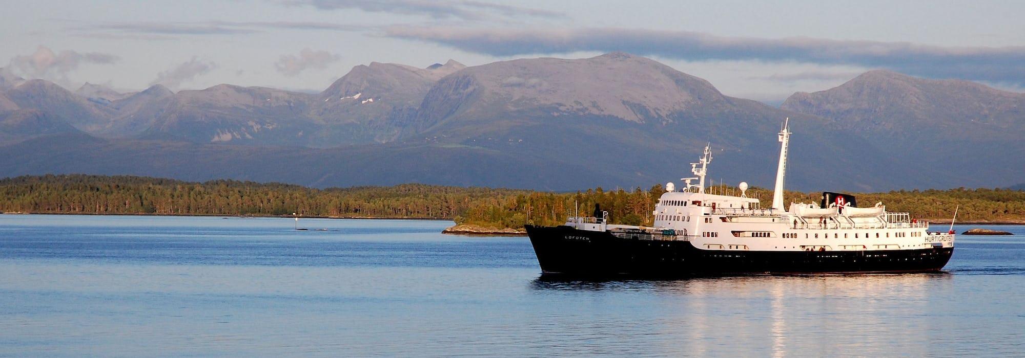 Fartyget MS Lofoten kryssar sig fram med träd och berg i bakgrunden.