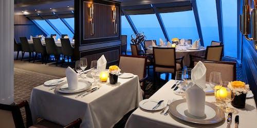 Bild från en av Azamara Quest lyxiga restauranger med stora fönster med utsikt över det blå havet.