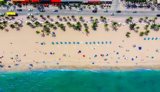 Bild från ovan på en strand i Fort Lauderdale med vatten i nederkant och massor av parasoll.
