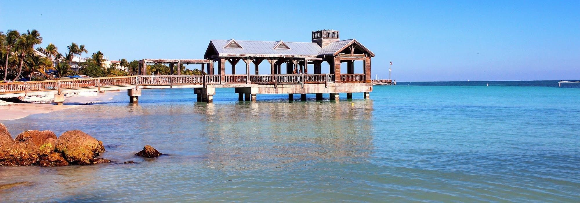 Bild på vatten, palmer och en träbyggnad ute på en brygga.