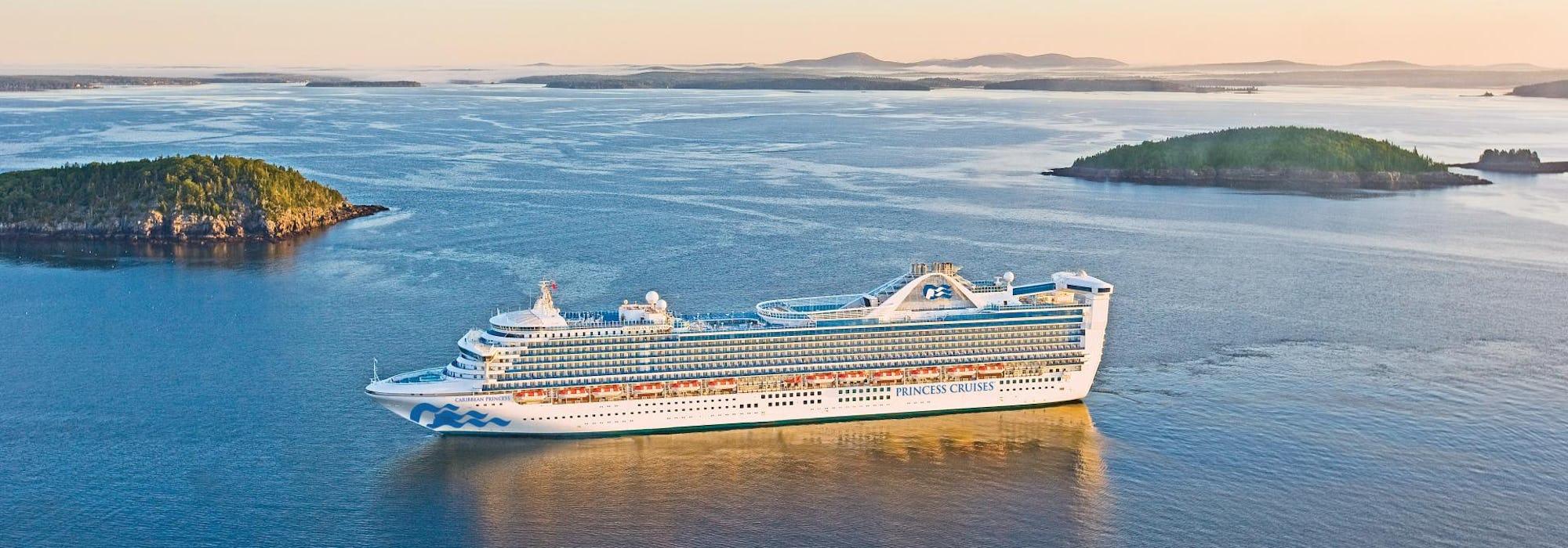 Fartyget Caribbean Princess glider fram i lugnt vatten mellan två gröna öar.