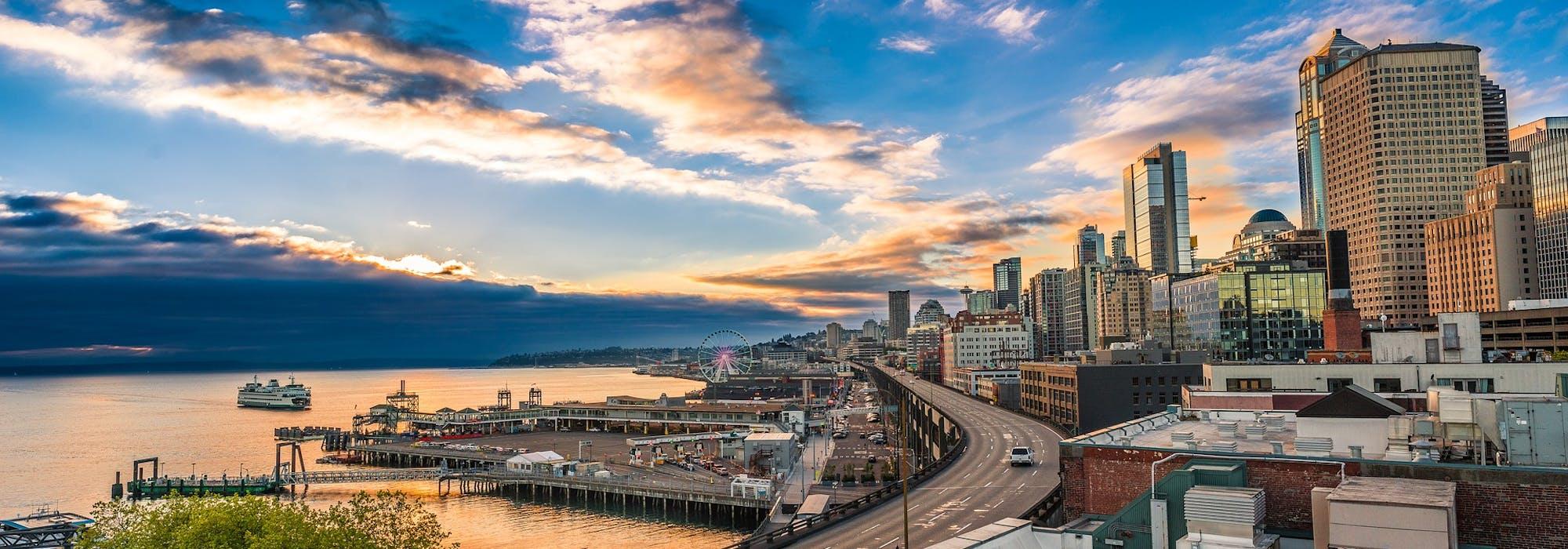 Bild på Seatlles hamn och skyskrapor i solnedgången.