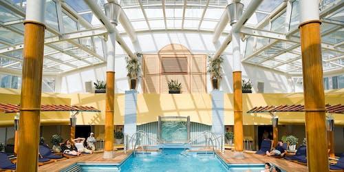 Bild på inglasad inomhuspoolen på Celebrity Constellation med människor i poolen och runtomkring i solstolar.