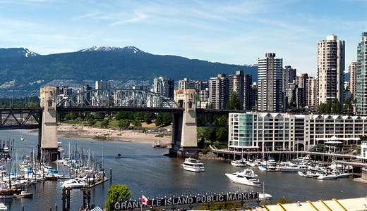 En mindre hamn i Vancouver med stadens skyskrapor till höger i bild och bergen som tornar upp sig.