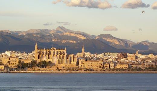 Vatten, höga byggnader och bergen i bakgrunden.