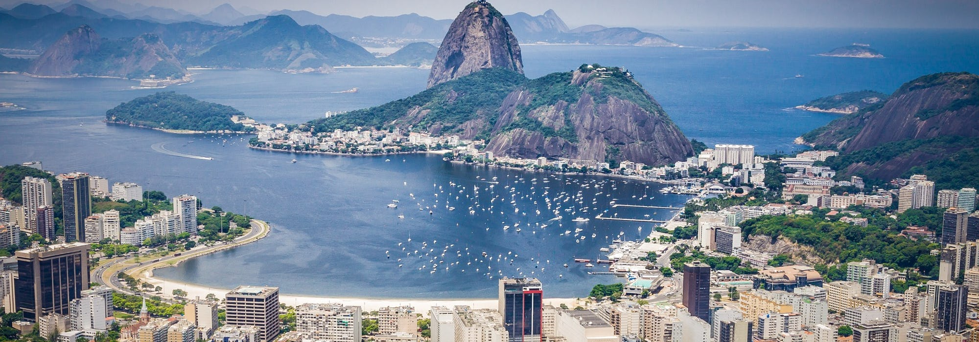 Bild ovanifrån på Rio de Janeiro i Brasilien med höga hus, stranden, berg och lagunen.