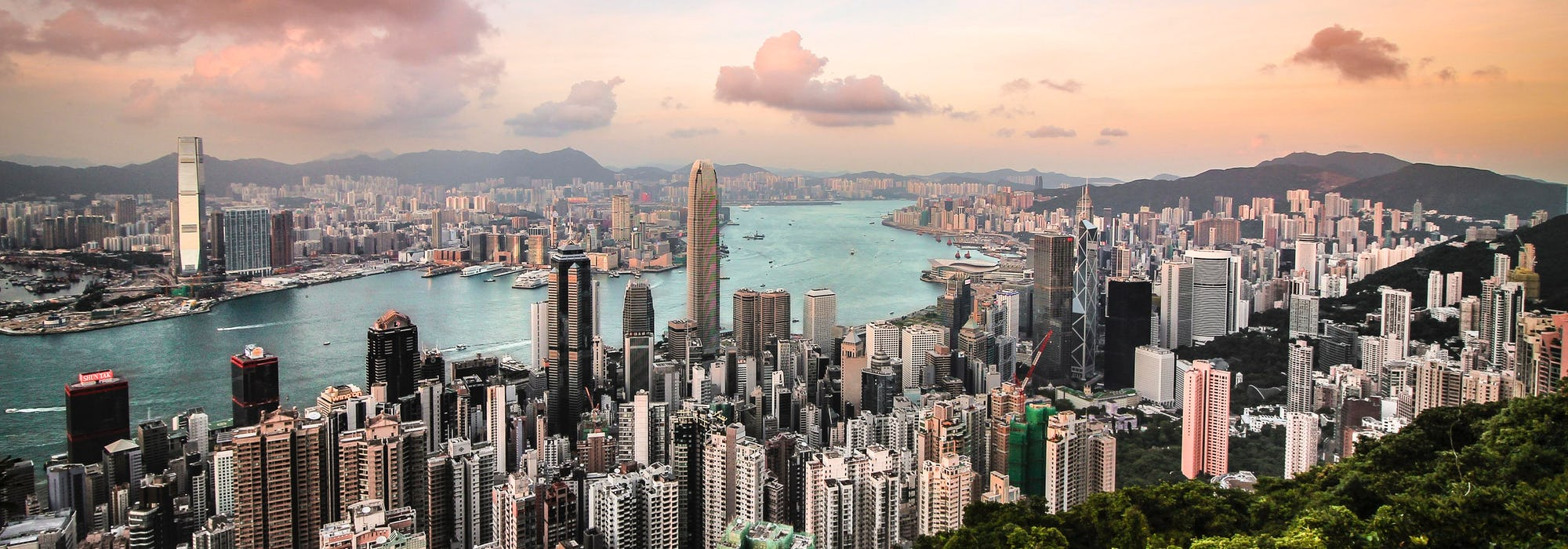 Bild på Victoria Harbour i Hong Kong tagen från luften med havet som skär mellan höghusen.