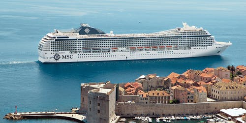 Bild tagen från sidan på MSC Musica som kryssar förbi en vacker hamn i Medelhavet.