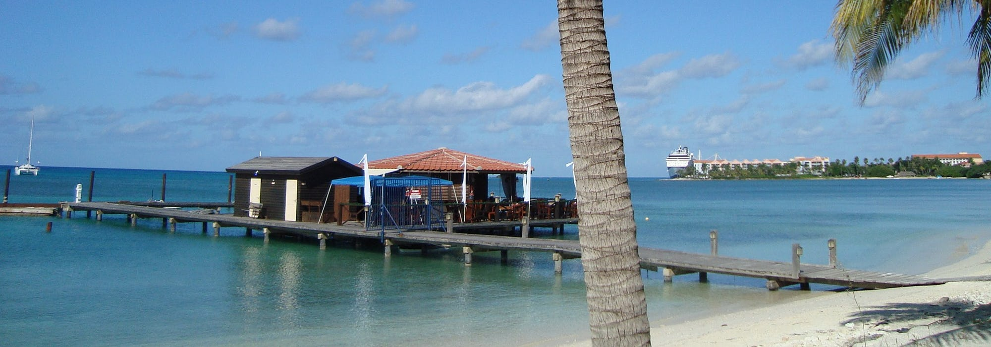 En bild från Oranjestad, Aruba med snövit strand, palmträd och lugnt, klart vatten.