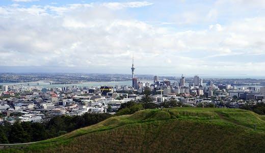 Aucklands skyline med höga byggnader, vatten och grönska.