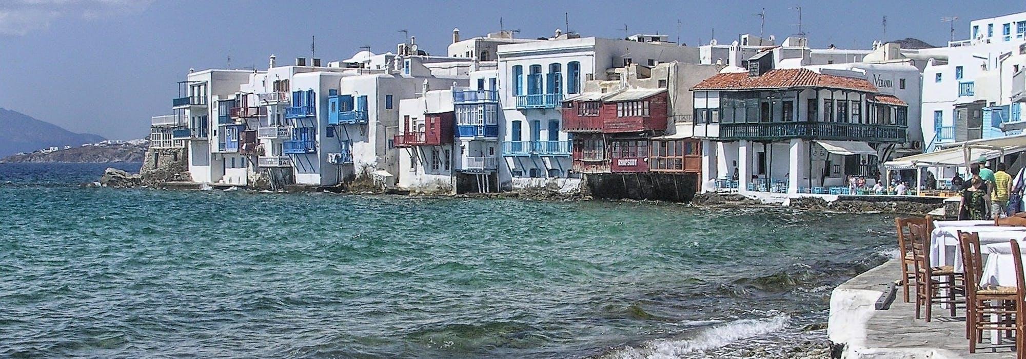 Vågorna slår in mot stranden med färgglada hus runtomkring i Mykonos, Grekland.