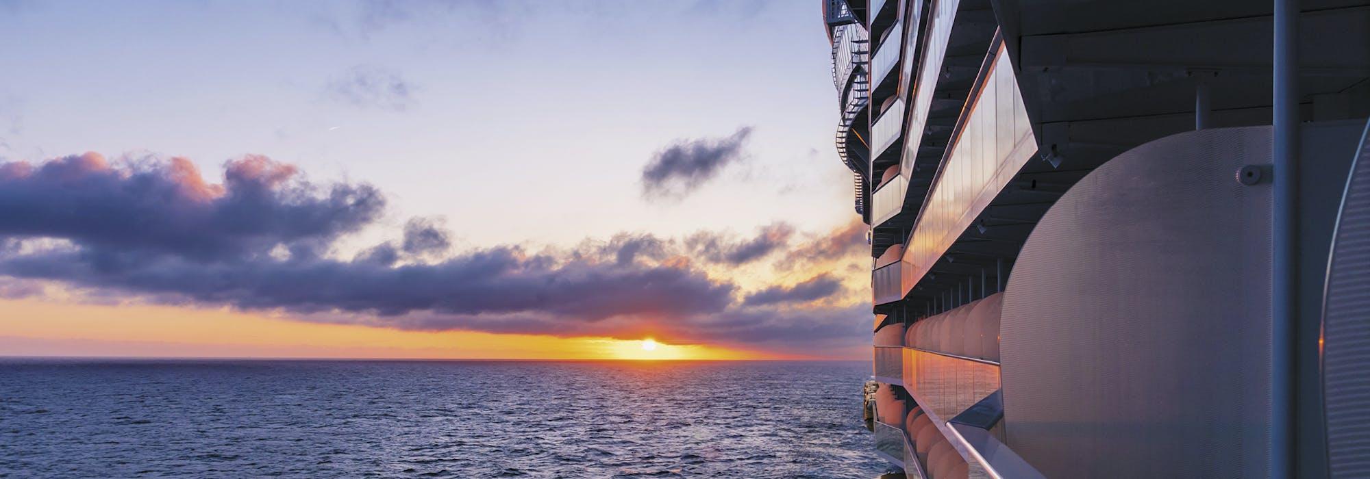 Bild på sidan av fartyget Symphony of the Seas med havet och en vacker solnedgång i bakgrunden.