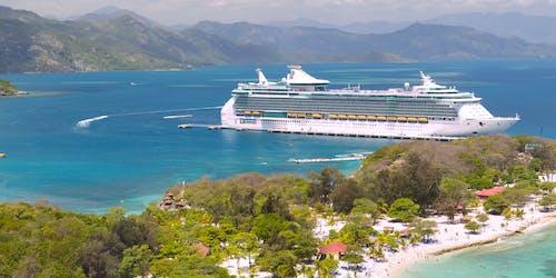 Fartyget Freedom of the Seas ligger vid en hamn i Karibien med ljusblått vatten och höga berg i bakgrunden.