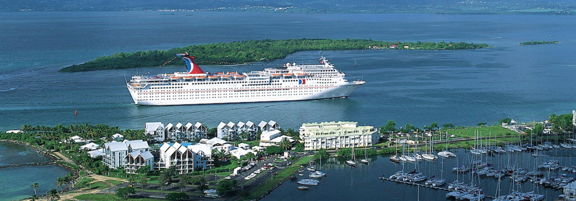 Bild på fartyget Carnival Fascination som kryssar fram mellan små gröna öar.