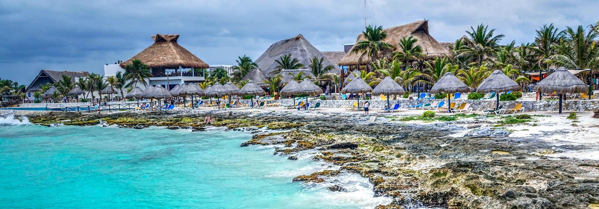 Bild på Costa Maya med klart vatten, klippor och palmer.