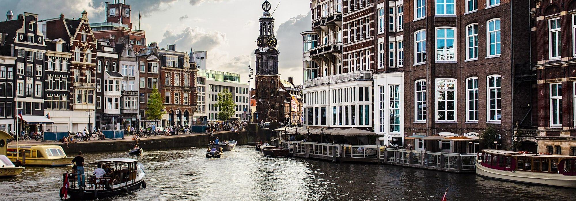 Kanalen i Amsterdam med färglada hus runtomkring.