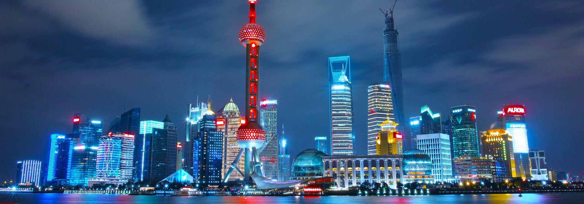 Bild tagen från vattnet på Shanghai's skyskrapor i kvällsljus. Byggnaderna lyser i olika färger.