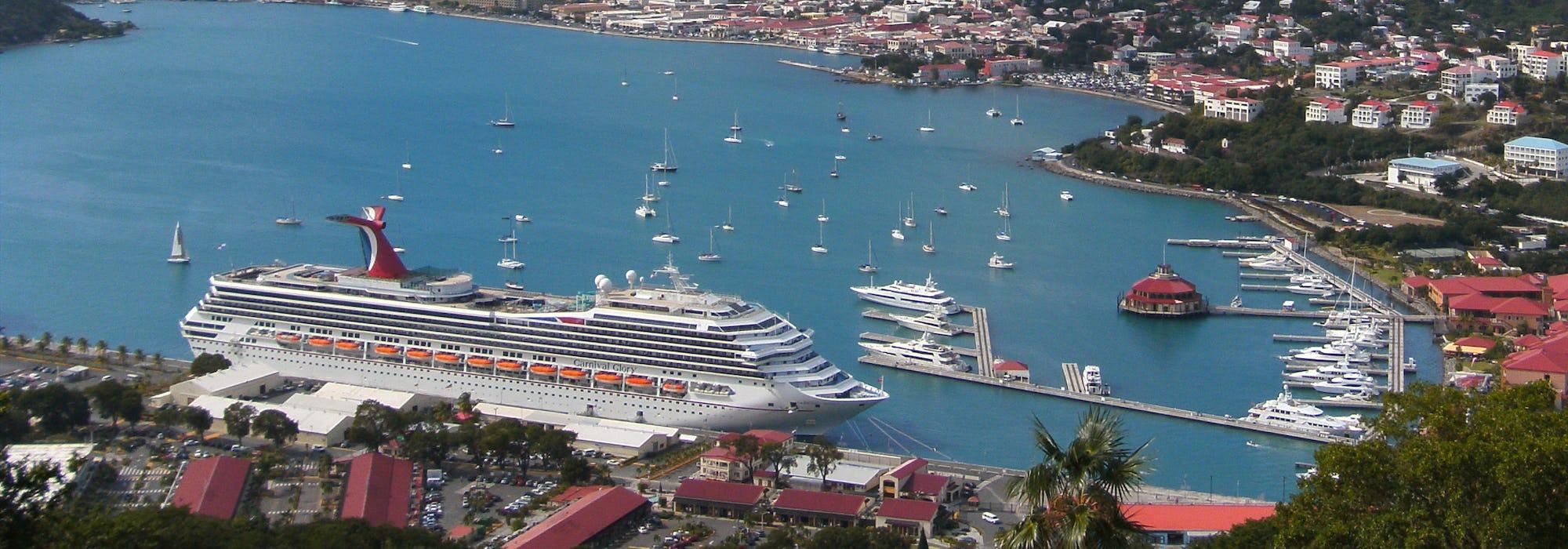 Carnival Glory ligger i hamn med höga berg och färgglada hus runtomkring.