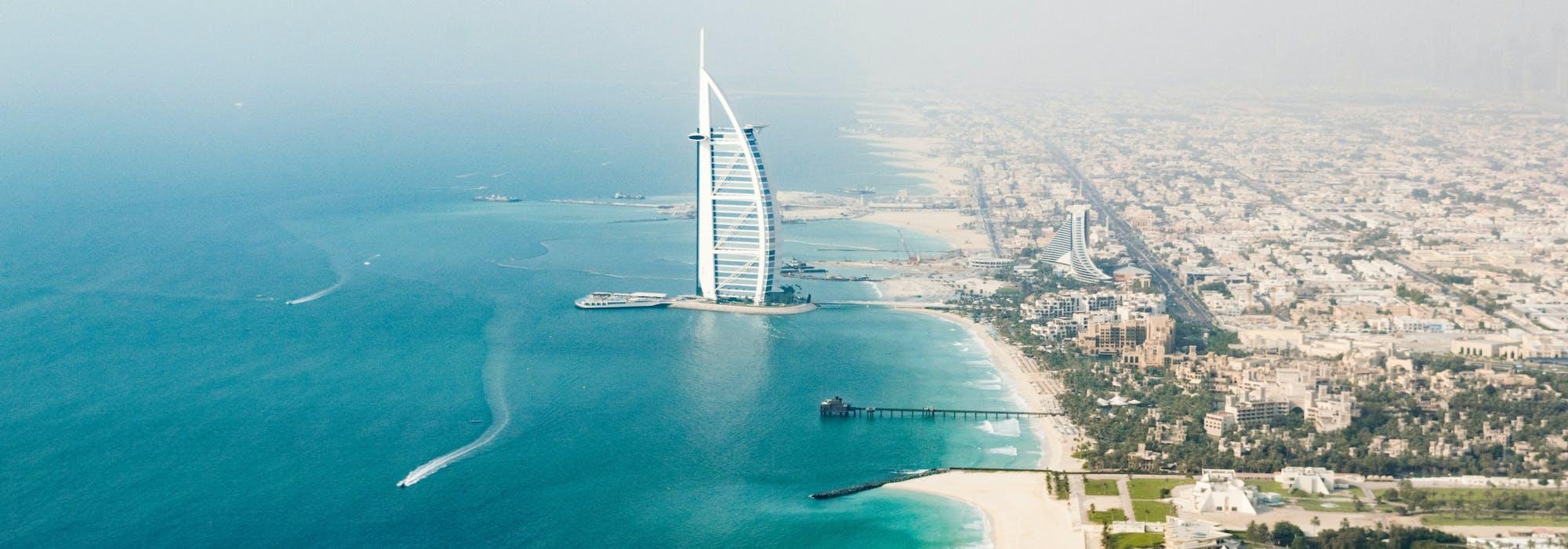 Överblicks bild över Dubais hamn med byggnader stränder och klarblått vatten.