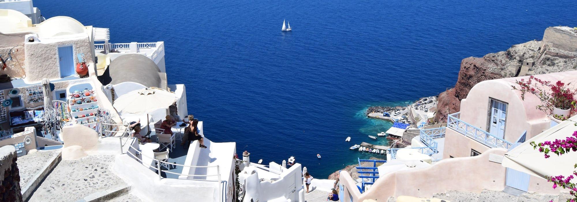 Vita byggnader i bakgrunden med klart blått vatten framför.
