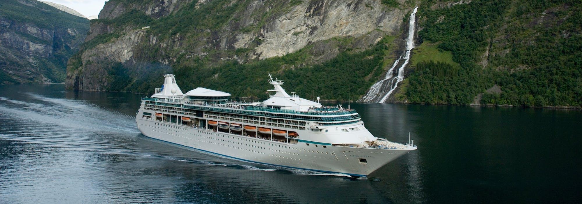 Vision of the Seas kryssar genom de storslagna norska fjordarna. I bakgrunden syns gröna berg och ett vattenfall.