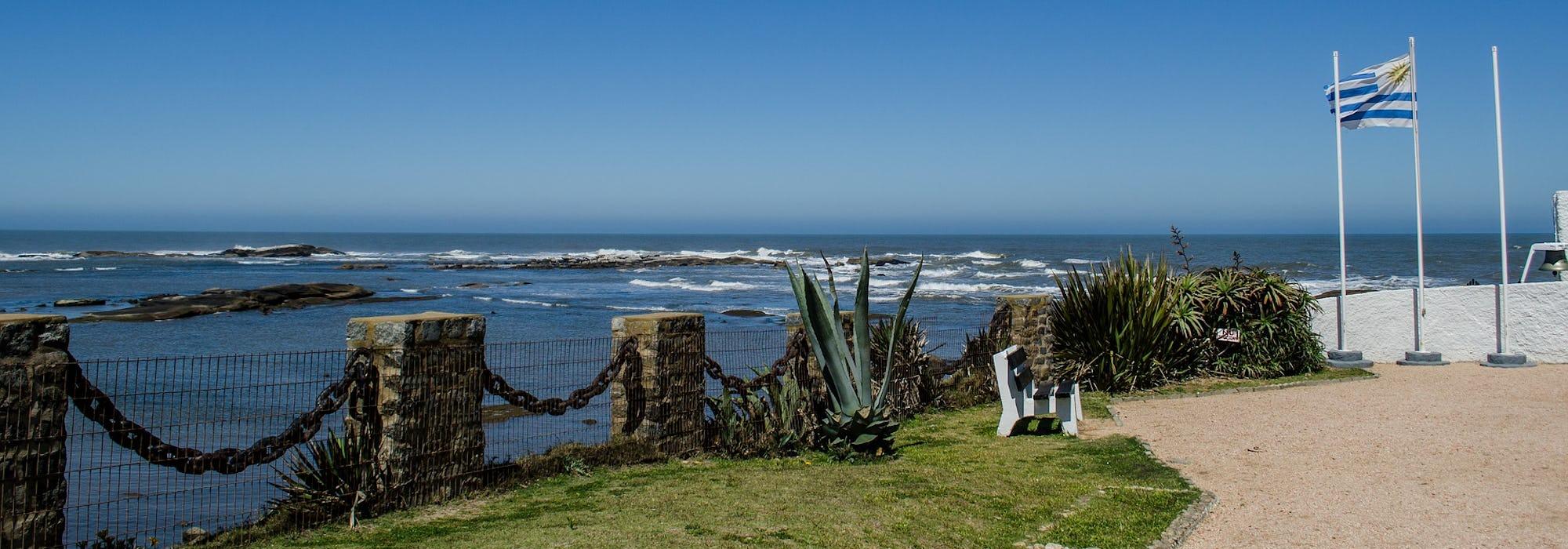 Montevideos kustlinje med havet och flaggan för Uruguay som vajar till höger.