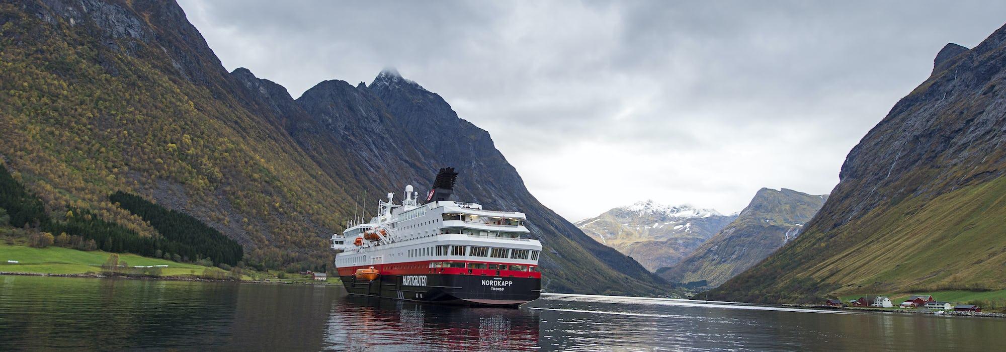 MS Nordkapp glider stilla genom de Norska fjordarna och dess vackra natur med berg runtomkring.