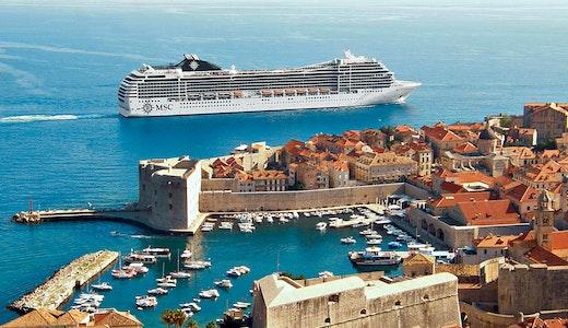Ett MSC fartyg utanför en vacker kust med byggnader i Medelhavet.