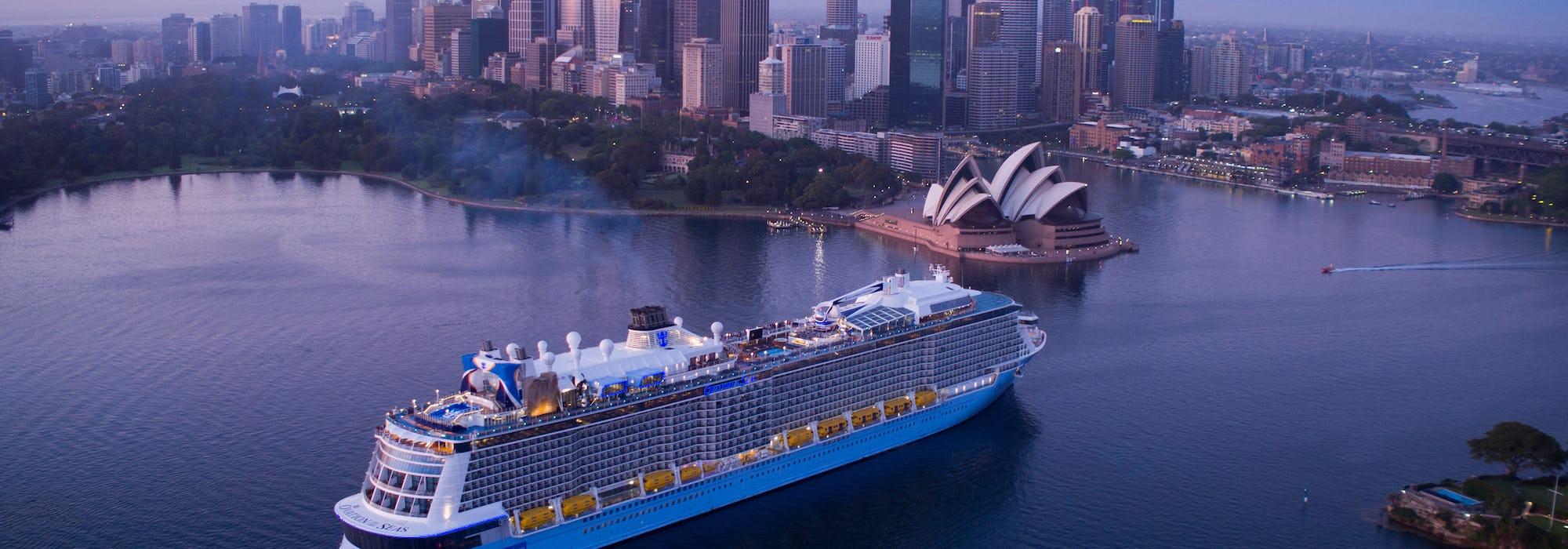 Ovation of the Seas kryssar förbi Sydneys ikoniska operahus med stadens skyskrapor som uppenbarar sig bakom.