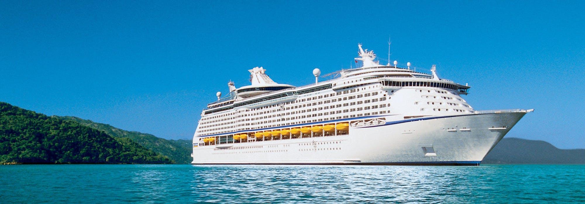 Fartyget Voyager of the Seas på håll med vackert blått vatten i förgrunden och smaragdgrön skog i bakgrunden.
