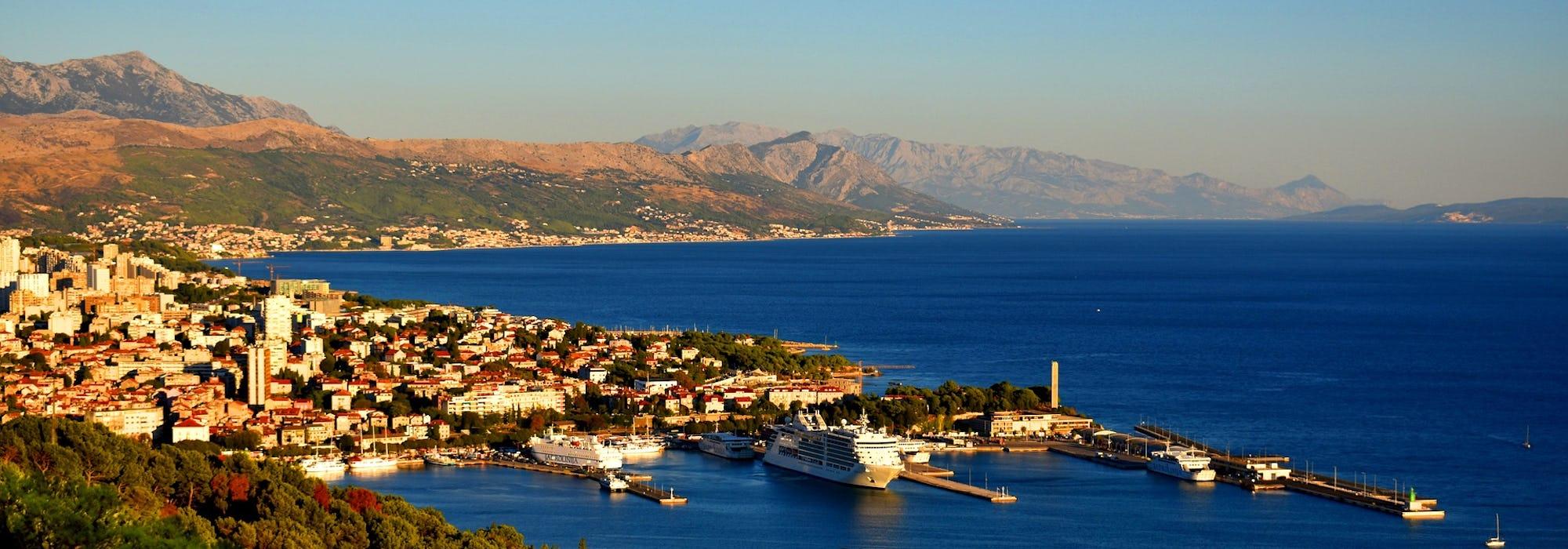 Bild ovanifrån på staden Split's hamn med berg och vatten i bakgrunden.