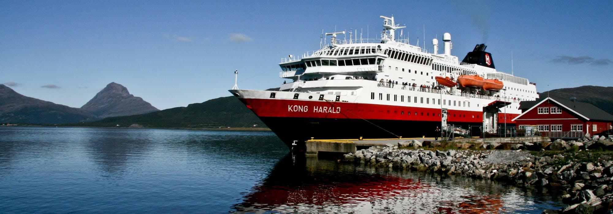 Fartyget MS Kong Harald står ankrad vid en lite hamn. I bakgrunden syns berg och grönska.