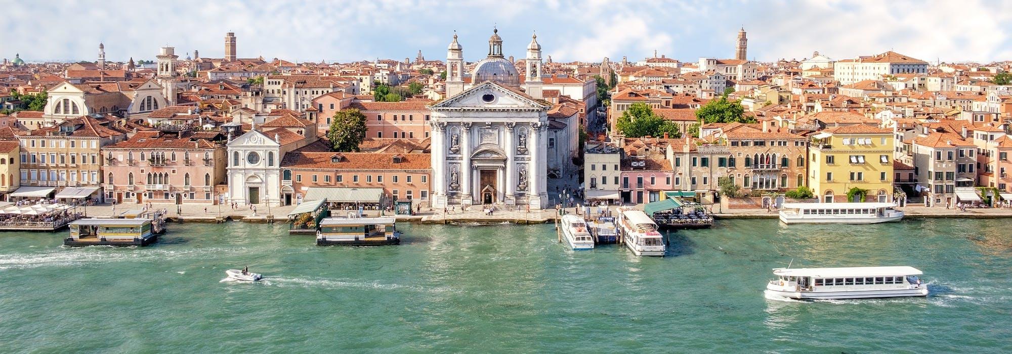 Bild på Venedig med det ljusgröna havet i framkant och byggnader i bakgrunden.