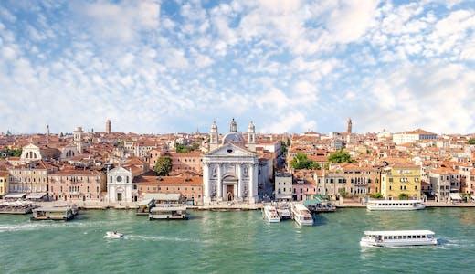 Bild på Venedig med det ljusgrön havet i framkant och byggnader i bakgrunden.
