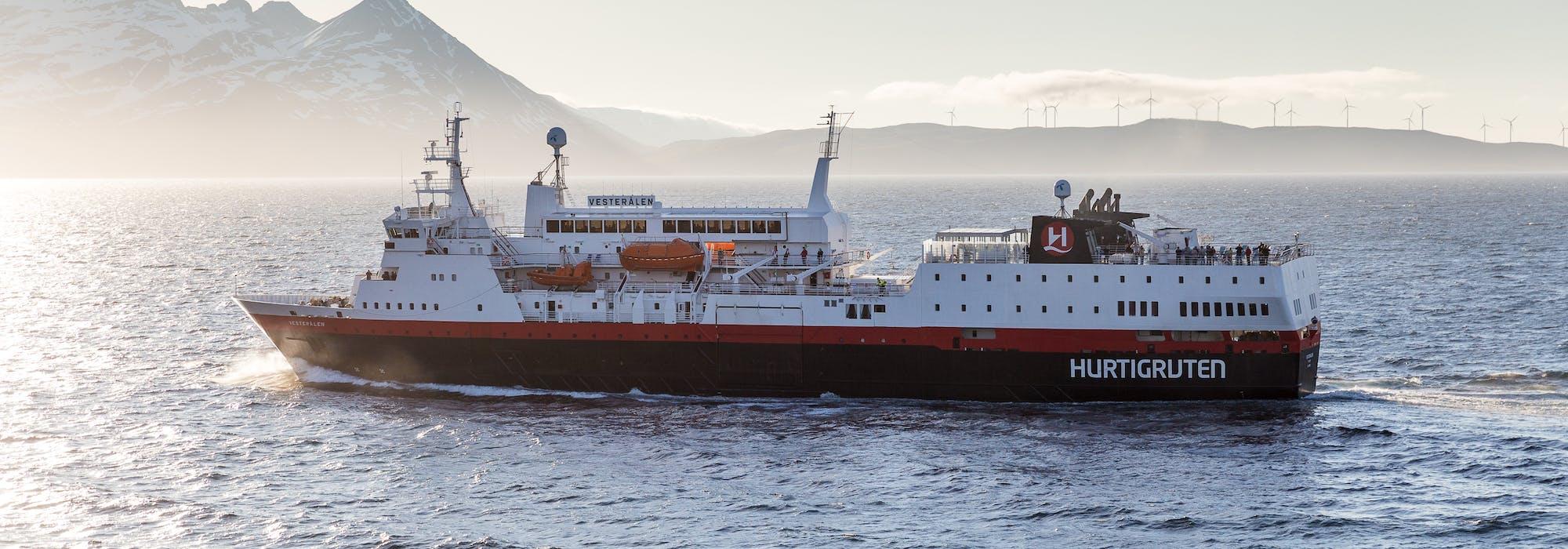 Hurtigrutens fartyg MS Vesterålen kryssar fram med snötäckta berg i bakgrunden.