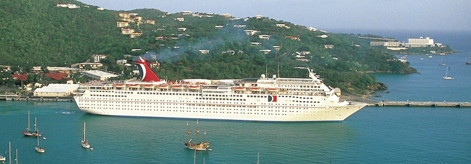 Fartyget Carnival Ecstasy ligger vid en hamn med en grön kulle i bakgrunden och mindre segelbåtar i framkant.