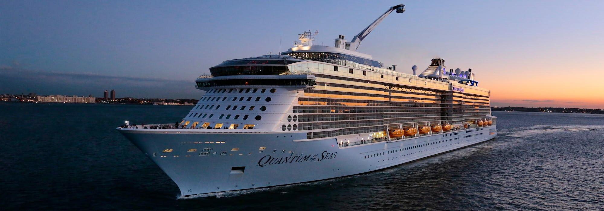 Bild på Quantum of the Seas tagen snett framifrån i solnedgången.