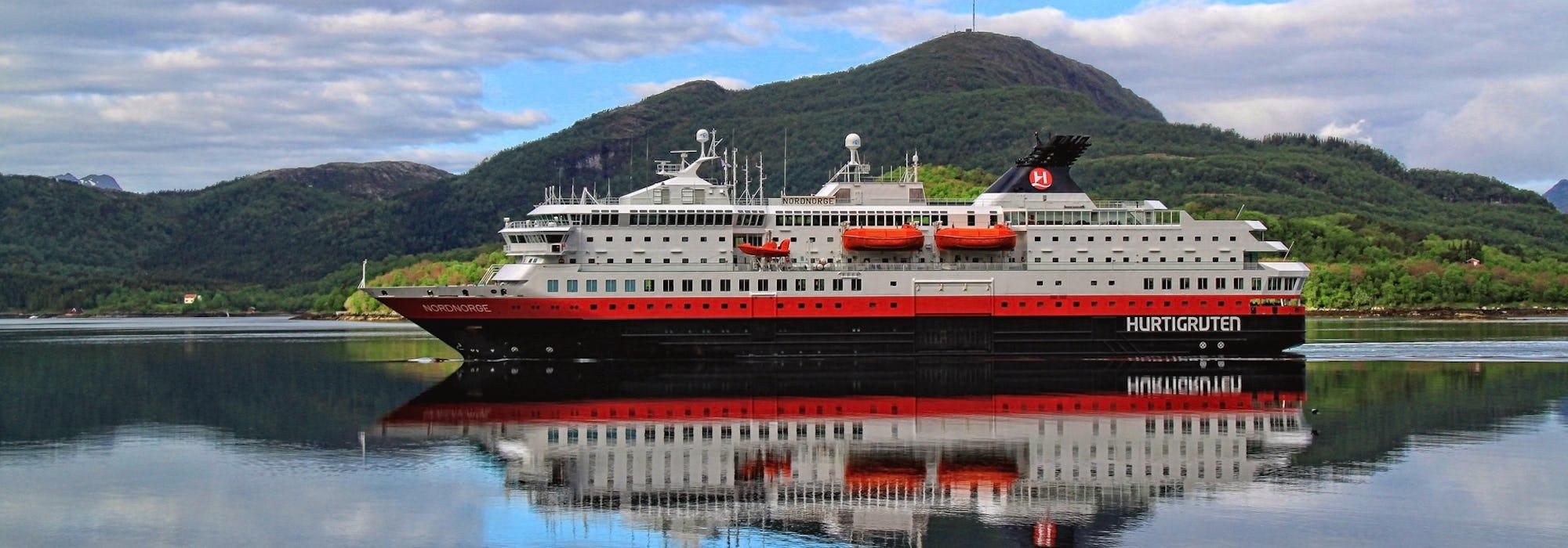Bild från sidan på Hurtigrutens fartyg Ms Nordnorge som stilla glider fram i vattnet med gröna berg i bakgrunden.
